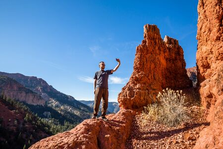 Hiker stopping to take a selfie with a cell phone on a cliff edge in southern Utah among red rock hoodoo formations. Фото со стока