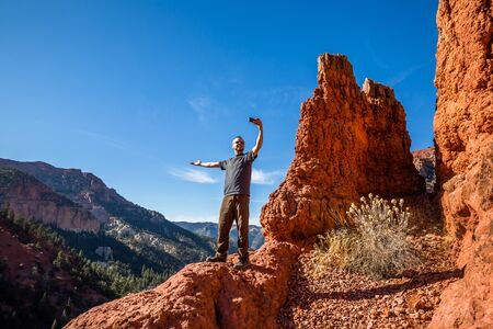 Excited hiker taking a selfie with an arm extended to show off the view behind him. Social media photos of active people.