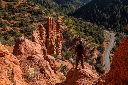 Hiker in sweater and vest standing above roadway in narrow red rock canyon in southern Utah.