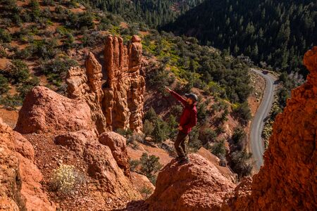Looking down on a hiker pointing upward among red rock hoodoo tower formations of southern Utah near Bryce Canyon.