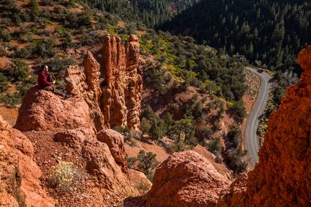 Man sitting atop red rock tower formation above winding canyon road far below. Фото со стока