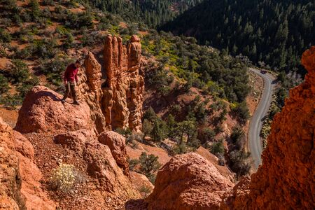 Man looking down over dangerous cliff edge among red rock towers of Southern Utah near Saint George.