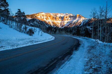 A cold winter night in December in Southern Utah desert. Many orange and red rock towers and hoodoos covered in snow near Cedar City, Utah. Фото со стока