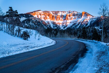Road traveling toward desert sandstone formations near Bryce Canyon and Cedar Breaks in Southern Utah desert. Snow covers the ground and pink light of alpenglow covers the mountain ahead. Фото со стока