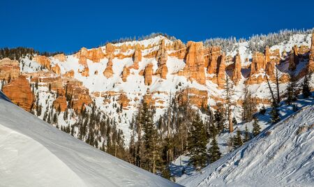 After a new storm brings in lots of snow, the sun shines on a clear day in Southern Utah. Red rock formations and cliffs surrounded by winter snow in January.