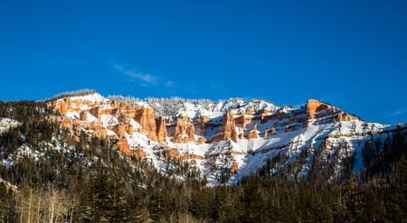 Snow among red rock cliffs and hoodoo towers of the Southwest desert in Utah. Red sandstone formations in winter. Фото со стока