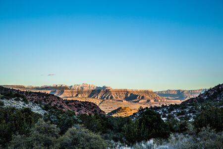 Looking out from the snow covered Pine Valley Mountains in Southern Utah. The skyline of Zion National Park and its steep sandstone formations are just visible in the distance.