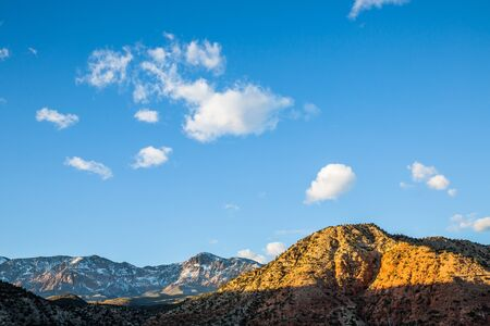 High above the desert of St. George, Utah, the snowy Pine Valley Mountains are lit by the last light of day