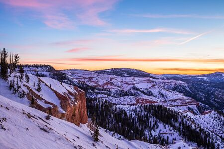 Pink and orange colorful clouds overhead at sunset. Below, orange and red rock covered in snow in Southern Utah winter scene. Фото со стока