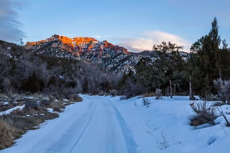 In the southern Utah desert in February, snow covers a small trail into the wilderness. Overhead, a large orange sandstone cliff is illuminated by the last light before sunset.