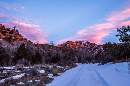 Bright pink clouds fill the sky above a desert canyon in Utah. Large sandstone cliffs ahead are dark red in the evening light.