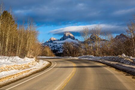 A winding paved road to Grand Targhee ski area looks up toward the summit of the Grand Teton in Wyoming.