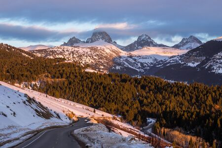 The three summits of the Teton Mountains in Wyoming just visible through the clouds before sunset. Below a narrow winding road leads to Grand Targhee ski area.