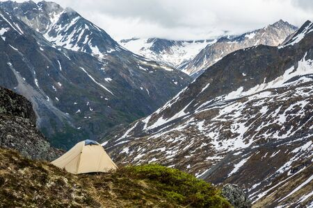 Tan and grey tent on narrow ledge of tundra and rock overlooking a large valley. Deep in the wilderness of the Talkeetna Mountains of remote Alaska.