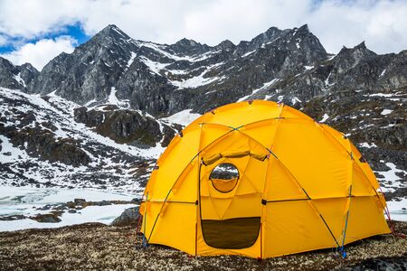 Large yellow dome tent shelter for many people set up in the wilderness of the Talkeetna Mountains in Alaska. Фото со стока