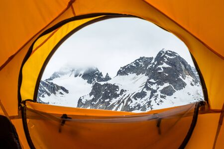 Looking out of a large yelow dome tent shelter at a massive rocky peak shrouded in clouds in the Talkeetna Mountains of Alaska.