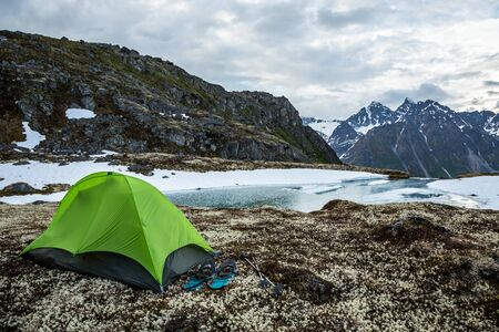 Green one-person backpacking tent with snowshoes over a partially frozen lake. Solo camping in spring time in remote Alaskan wilderness.