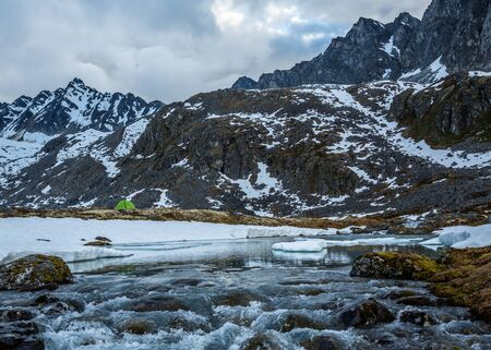 Camping overa frozen lake and waterfall below massive rocky peaks in the remote Alaskan wilderness of the Talkeetna Mountains.