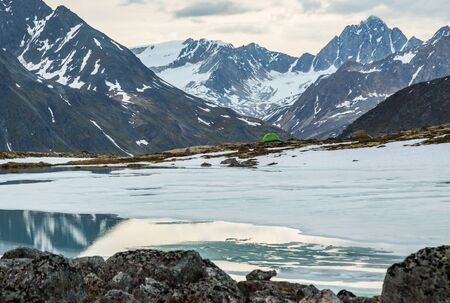 Small green one-person tent above mostly frozen lake in the Alaskan wilderness. Beyond camp are snowy glaciers and craggy summits. Фото со стока