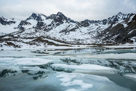 A small alpine lake thawing in spring below Montana Peak in the Alaskan wilderness of the Talkeetna Mountains.