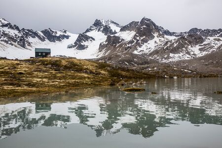 Small green backcountry hut in remote Alaska, reflected in a calm alpine lake in the Talkeetna Mountains.