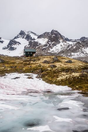 Small green building for shelter in the wild Alaskan backcountry below a large peak covered in glaciers.
