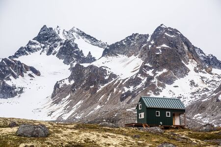 A small green building in the Alaskan wilderness provides shelter for backcountry skiers and hikers in the Talkeetna Mountain Range. Фото со стока