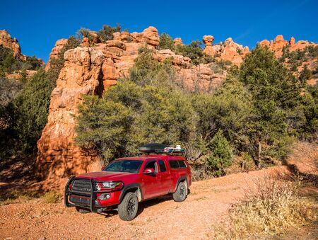 Orange sandstone towers stand above a narrow dirt trail where a red pickup camper is parked. The truck is loaded with camping and overland gear for offroad treks. Фото со стока