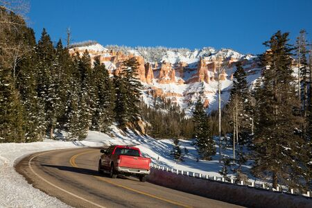 Red pickup driving up a winding canyon road toward snow covered rock formations in the red and orange sandstone.