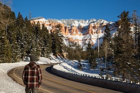 Man in red plaid shirt and warm cap standing on the side of a highway. The road leads toward a sandstone rock formation of red and orange towers covered in snow.