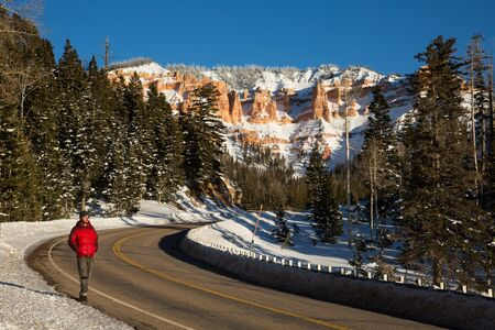 Walking along the side of a road in the Utah desert in a red winter jacket before sunset on a cold night.