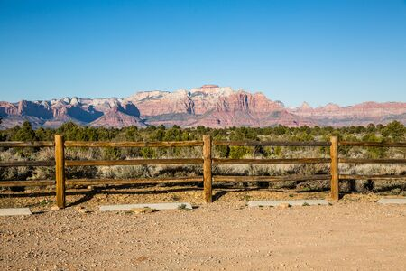 Wooden fence along the edge of an empty trailhead parking area in the desert of Southern Utah. Фото со стока