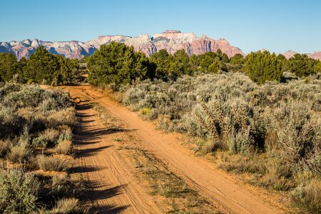 ATV doubletrack trail through the desert of the American Southwest. Large sandstone cliffs of red and white stand in the distance.