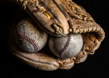 Two scuffed and worn out baseballs in an old leather glove on dark background.