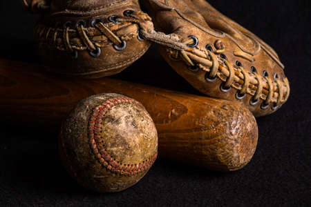 Nostalgic baseball gear from a childhood of many neighborhood games. Baseball, glove and bat all scratched and stained from years of play