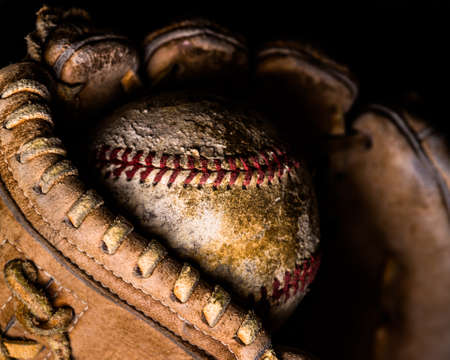 Basball caught just in the end of an old leather glove, lit from the side.