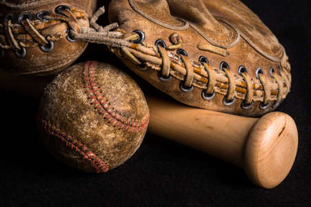Contrast of old and new equipment with old mitt and ball joined by brand new baseball bat.