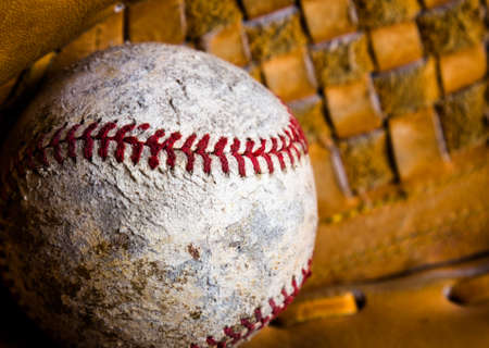 Closeup of baseball in a mitt. The ball is old and damaged, well used with scuffs, stains, and stitching out in places.