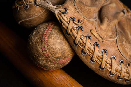 Baseball mitt holding a worn out baseball on top of an old scratched up bat.