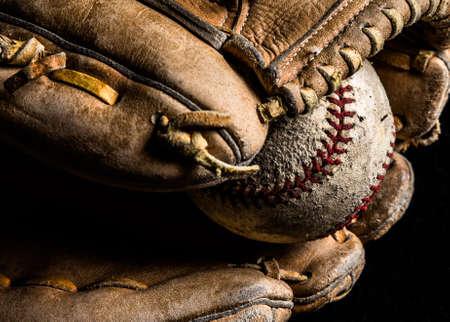 Baseball mitt holding a scuffed up old baseball. 版權商用圖片