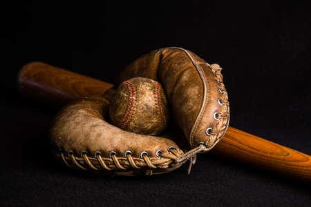 Antique catcher's mitt holding a baseball lying on an old wood bat.