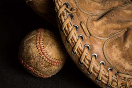 Old style baseball glove near stained and well used ball.