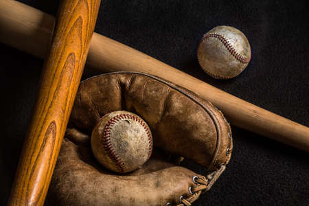 Two baseballs and a glove along with an old and new baseball bat. All but the new bat is scratched and worn from years of love of the game. Фото со стока
