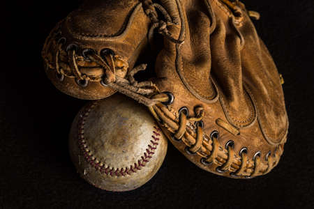 Worn out catchers mitt resting on a scuffed up stained old baseball