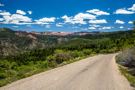 Small road leading through green hills to the red rock cliffs of Cedar Breaks National Monument in Southern Utah.