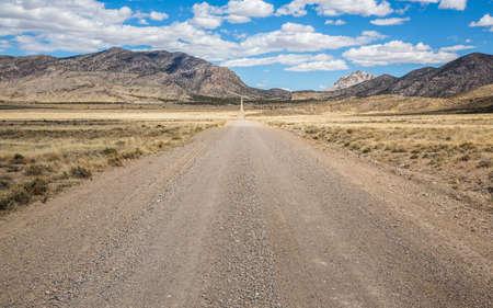 Dirt road cutting through barren Utah desert toward the distant Crystal Peak