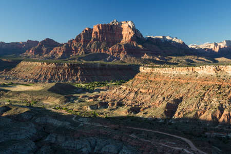 Sun sets over the Zion National Park skyline with its many red rock cliffs and monuments. 版權商用圖片