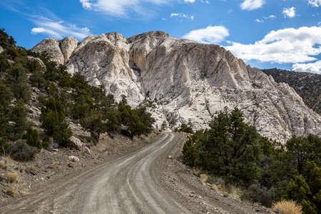 White limestone of Crystal Peak looms over a dirt road through Utah's West Desert. Фото со стока