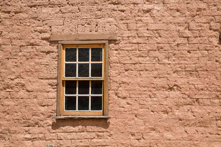 In a small ghost town in the Southern Utah wilderness, a wooden window is set into a red brick building.