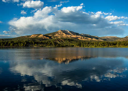 A calm lake begins to stir with wind from a developing thunderstorm. The red rock summit of a distant peak is reflected in the water. Фото со стока